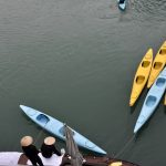 locals and kayaks in ha long bay
